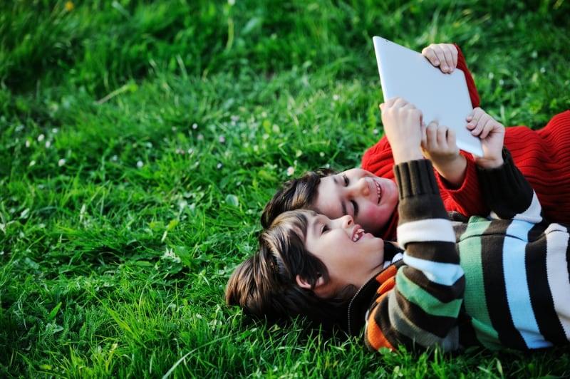 Barn ligger i gresset og ser på nettbrett