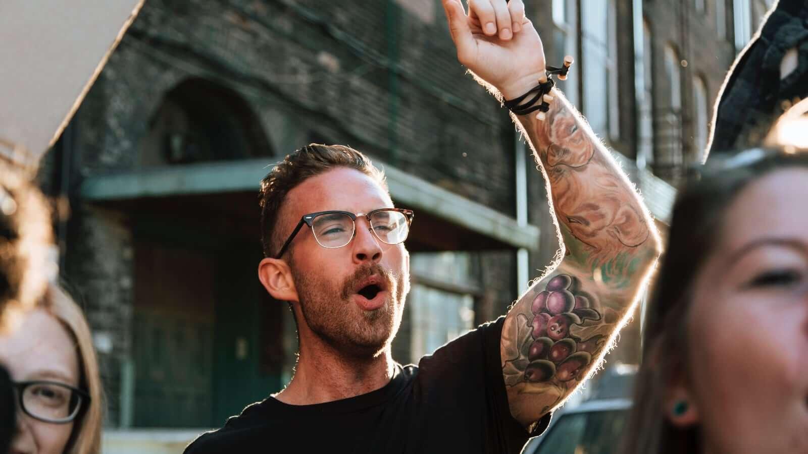 Ung, trendy man rekker tatovert arm i været